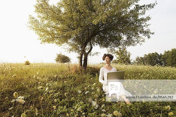 Frau mit Laptop entspannt auf dem Feld