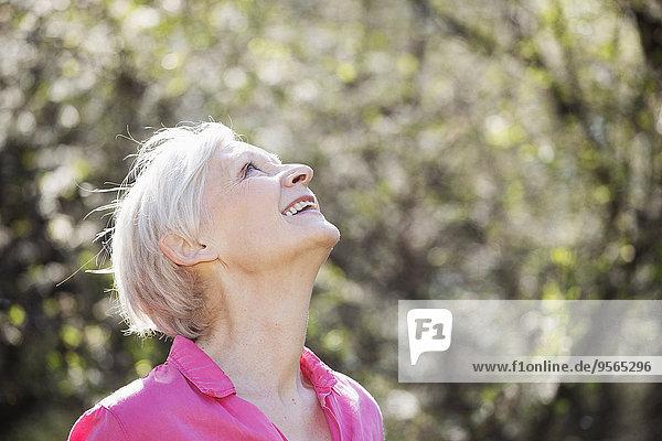 Glückliche reife Frau  die im Park nach oben schaut.