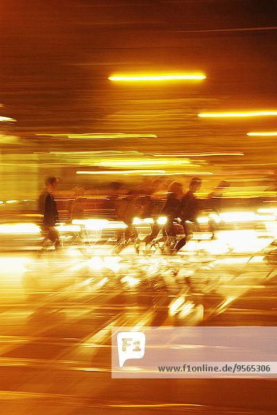 Verschwommene Bewegung von Personen  die im beleuchteten Tunnel gehen
