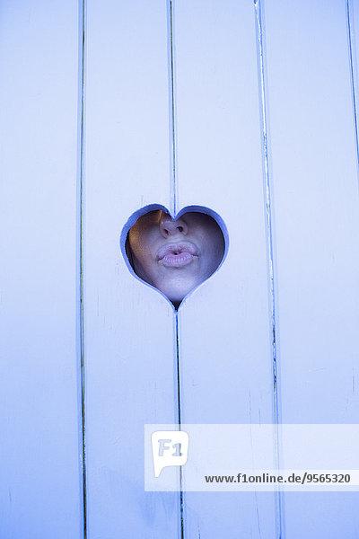 Nahaufnahme einer Frau  die ihre Lippen durch herzförmiges Holz kräuselt.