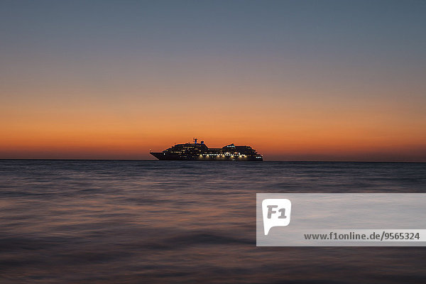 Silhouette-Kreuzfahrtschiff auf See bei Sonnenuntergang