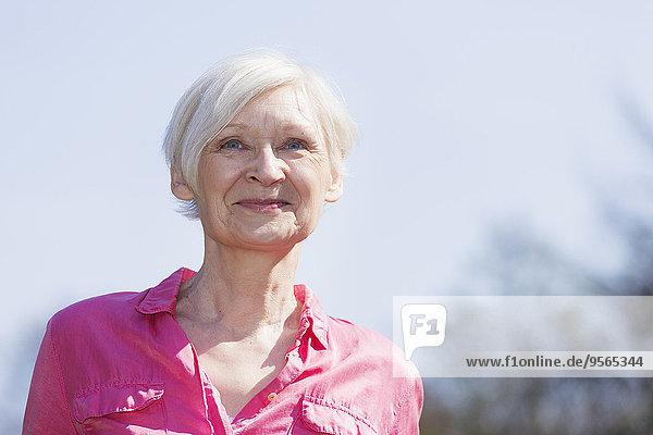 Reife Frau lächelt  während sie gegen den Himmel schaut.