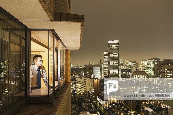 Geschäftsmann betrachtet beleuchtetes Stadtbild durch das Fenster in der Abenddämmerung