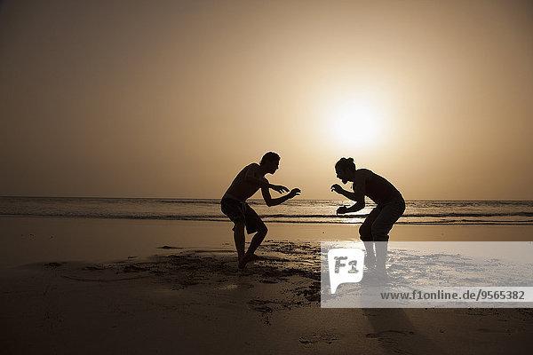 Volle Länge der Silhouette männliche Freunde spielen am Strand bei Sonnenuntergang