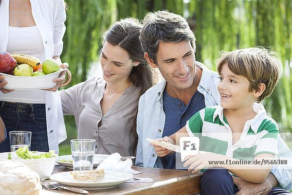 Familie isst zusammen im Freien  Vater hält Sohn auf Schoß