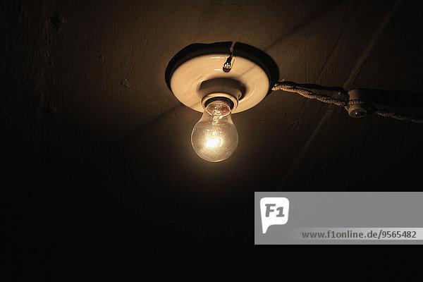 Niederwinkelansicht der beleuchteten Glühbirne an der Decke