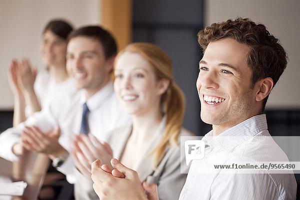 Junge Geschäftsleute applaudieren während des Treffens