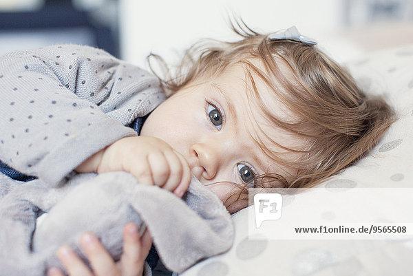 Kleines Mädchen liegend  Daumen lutschend  Portrait