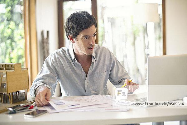 Geschäftsmann  der zu Hause am Laptop arbeitet