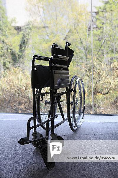 Gefalteter Rollstuhl an der Glaswand