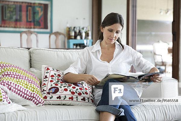 Frau sitzt auf dem Sofa und liest Magazin