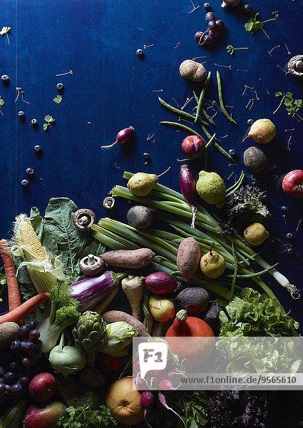 Hochwinkelansicht von frischem Gemüse und Obst auf blauem Tisch verstreut