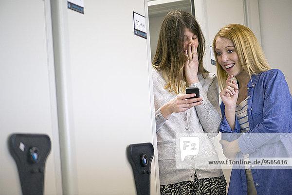 Frauen lachen über Smartphone im Büro