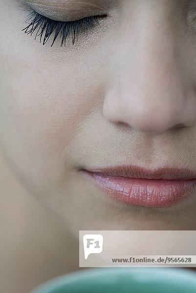 Woman smelling hot drink  close-up