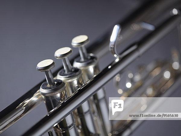 Nahaufnahme der Trompete vor grauem Hintergrund