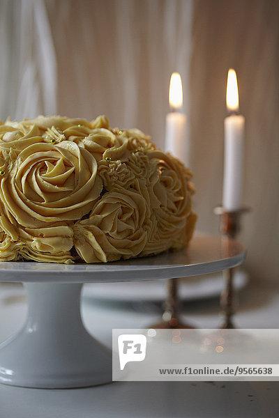 Rosenkuchen und Kerzen auf dem Tisch