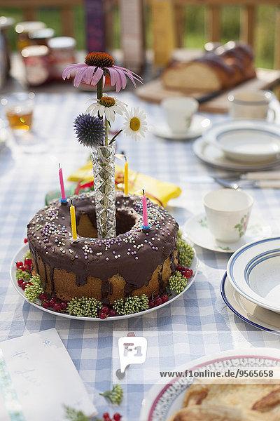 Dekorierte Geburtstagstorte auf dem Esstisch im Hof