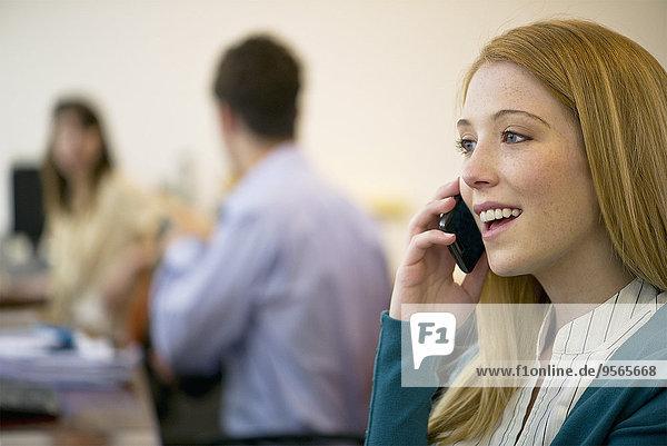 Junge Frau spricht am Handy im Büro