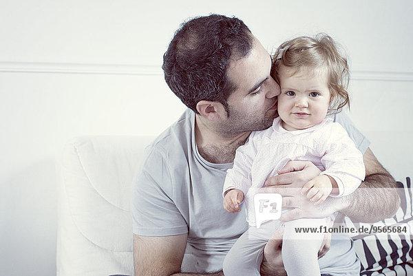 Vater hält das Mädchen auf dem Schoß und küsst seine Wange.