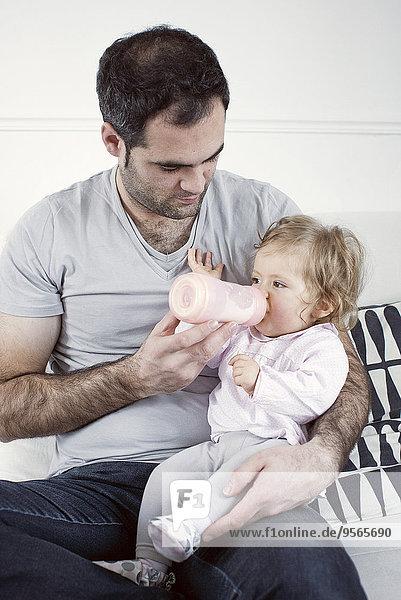 Vater hält das Mädchen auf dem Schoß und füttert es mit der Flasche.