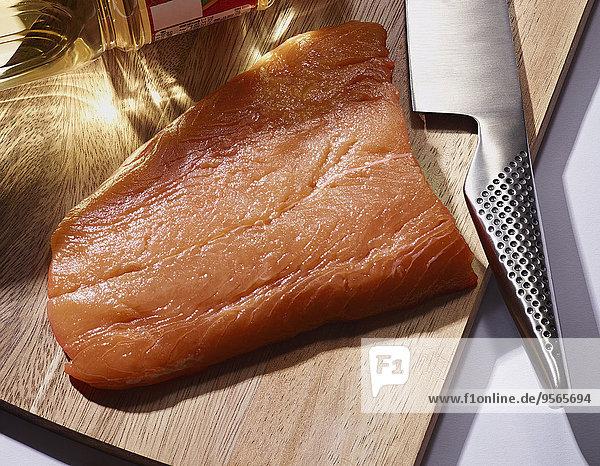 Hochwinkelansicht von Lachsscheibe und Messer auf dem Schneidebrett