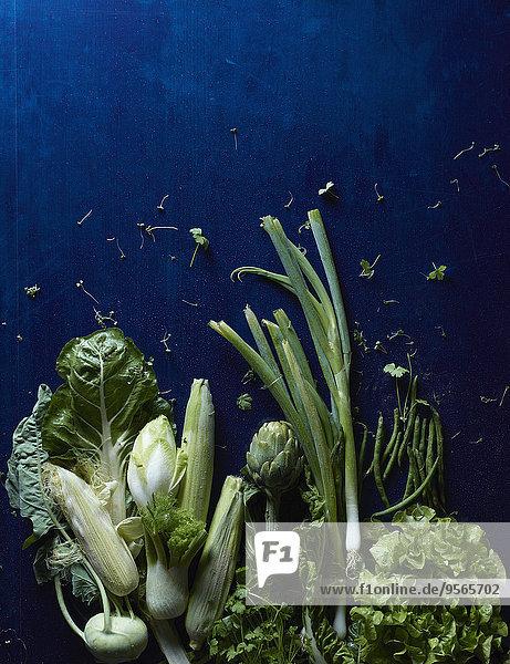Direkt über dem Schuss grünen Gemüses auf blauem Tisch