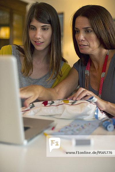 Mutter und Tochter lernen gemeinsam Stickerei  indem sie sich Online-Videos anschauen.