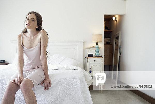 Frau am Bettrand sitzend