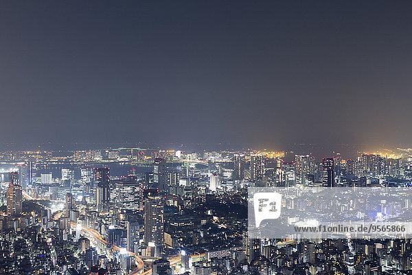 Luftaufnahme des beleuchteten Stadtbildes gegen den Himmel bei Nacht