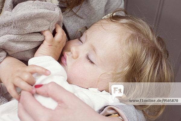 Babymädchen schläft in den Armen der Mutter  abgeschnitten