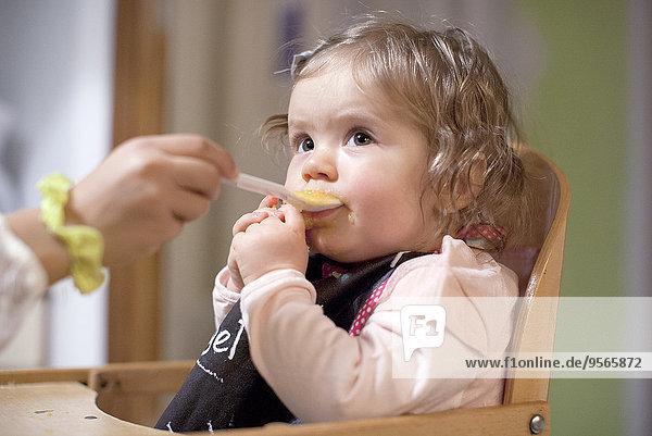 Kleines Mädchen  das von einem Elternteil gefüttert wird.