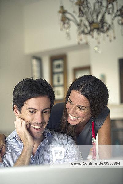 Paar  das Laptop-Computer lächelnd betrachtet