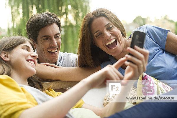 Junge Frau teilt Fotos auf dem Smartphone mit Freunden
