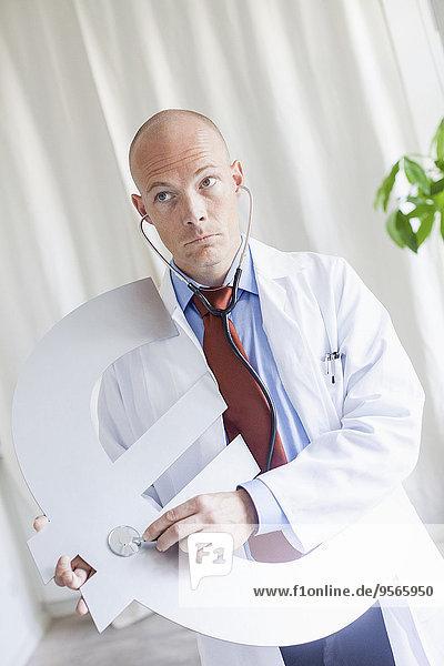 Reife Ärztin untersucht Euro-Symbol mit Stethoskop in der Klinik
