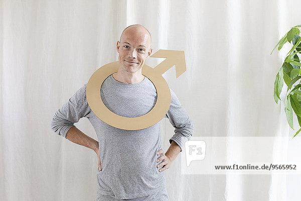 Porträt eines lächelnden Mannes mit männlichem Symbol im Nacken zu Hause