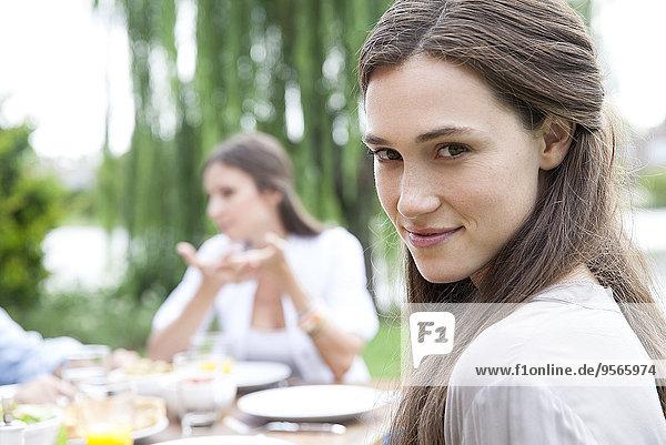 Junge Frau am Tisch im Freien sitzend  über die Schulter lächelnd  Portrait