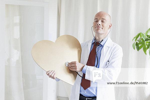 Arzt mit geschlossenen Augen untersucht Herzform mit Stethoskop in der Klinik