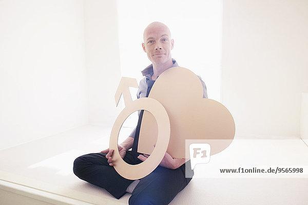 Porträt eines selbstbewussten Mannes mit Herzform und männlichem Symbol im Amt