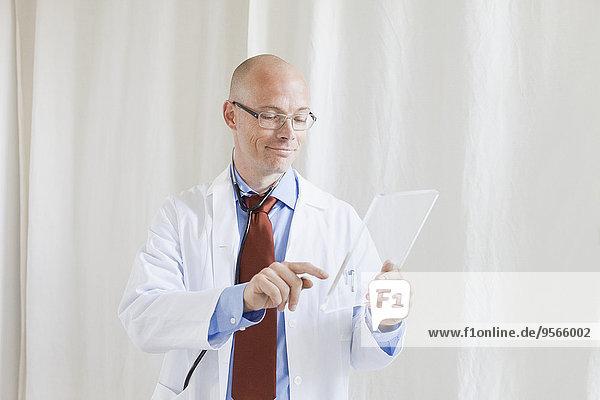 Männlicher Arzt berührt futuristisches digitales Tablett in der Klinik