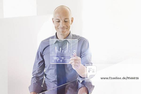 Lächelnder Geschäftsmann betrachtet futuristisches digitales Tablett am Schreibtisch im Büro