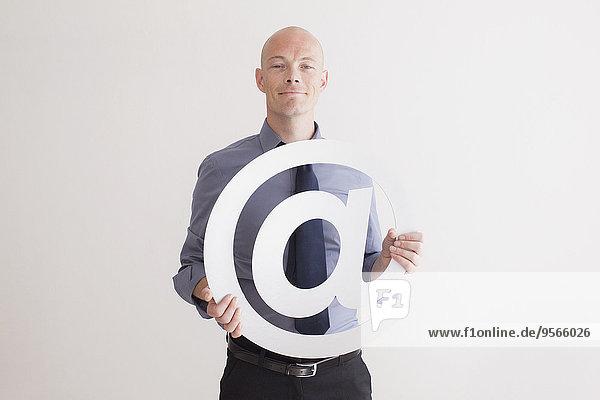 Porträt eines selbstbewussten Geschäftsmannes mit Symbol auf weißem Hintergrund
