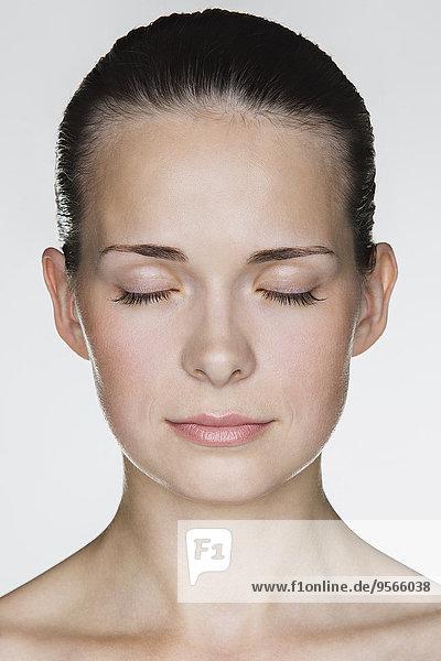 Nahaufnahme der schönen jungen Frau mit geschlossenen Augen vor weißem Hintergrund