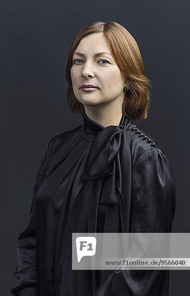 Porträt einer selbstbewussten Frau vor farbigem Hintergrund