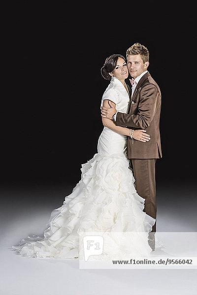 Durchgehende Seitenansicht von Braut und Bräutigam auf schwarzem Hintergrund
