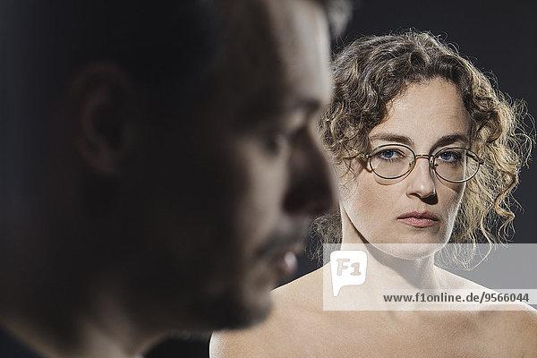 Porträt einer ernsten Frau mit Mann im Vordergrund