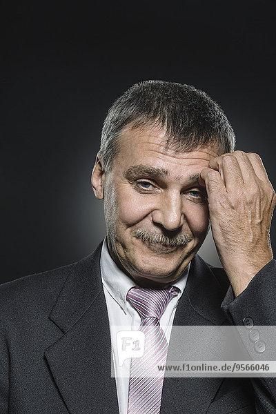 Porträt eines lächelnden Geschäftsmannes  der den Tempel vor schwarzem Hintergrund kratzt.