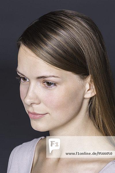Nahaufnahme der nachdenklichen jungen Frau vor schwarzem Hintergrund