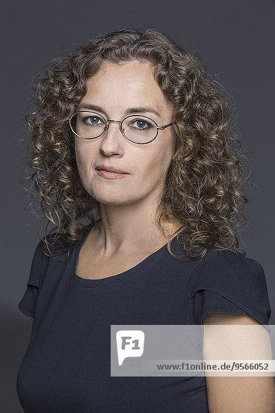 Porträt einer selbstbewussten Frau vor grauem Hintergrund