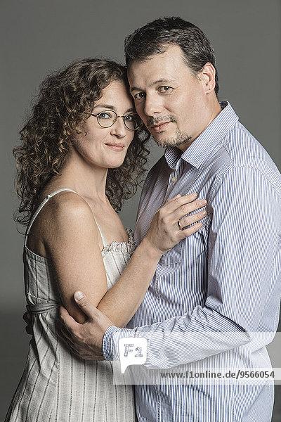 Seitenansicht Porträt eines liebenden Paares  das sich vor grauem Hintergrund umarmt.