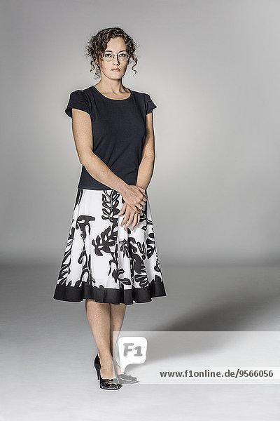 Ganzflächiges Porträt einer selbstbewussten Frau vor grauem Hintergrund